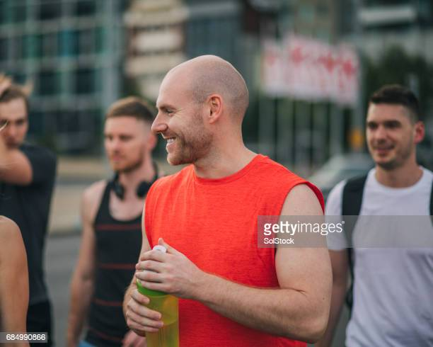walking to the gym with his friends - completely bald stock pictures, royalty-free photos & images