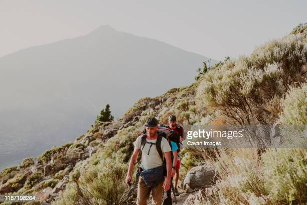 walking to the top of guajara mountain with the awesome teide in back - pico de teide stock pictures, royalty-free photos & images