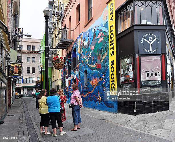 A walking tour guide talks to a small group of tourists in Jack Kerouac Alley which runs between two San Francisco landmarks City Lights Bookstore...