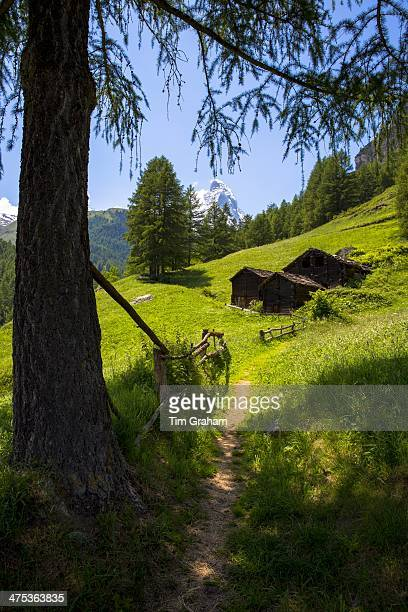 Walking trail passes chalet barns below the Matterhorn mountain in the Swiss Alps near Zermatt Switzerland