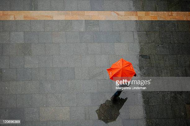 Walking under an orange umbrella seen from above