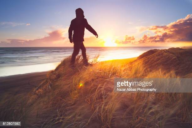 Walking Up On Sand Dunes With Sunset In Background.