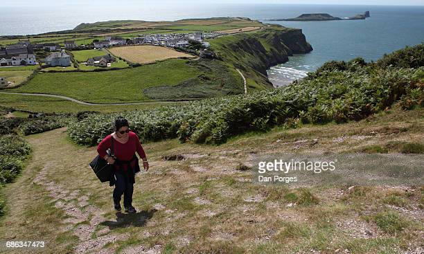 walking uphill with a beautiful view behind - gower peninsula stock photos and pictures