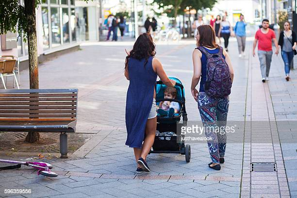 Walking women with baby buggy and child