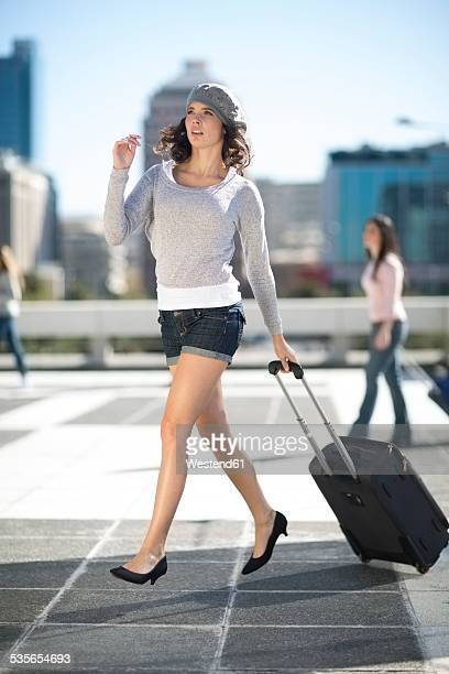 walking young woman with rolling suitcase - hot pants stock pictures, royalty-free photos & images
