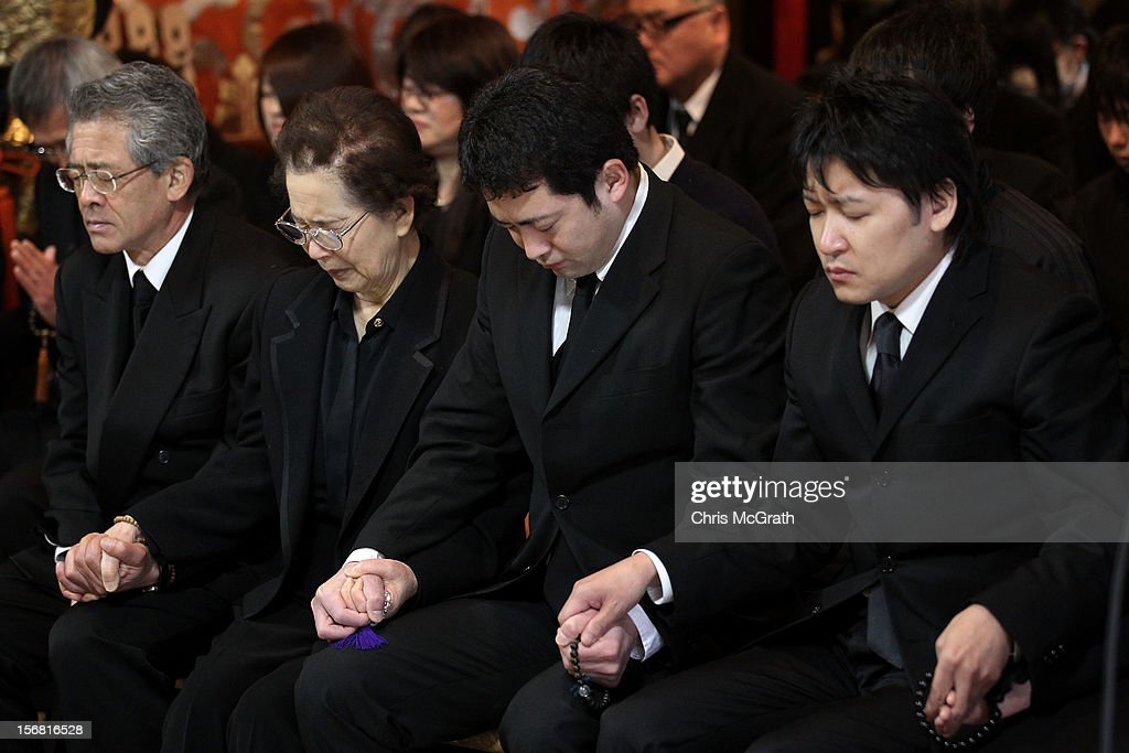 Walkley Press Photographer of The Year Portfolio on November 22, 2012 in Singapore. Image Caption: People hold hands as a monk speaks during a ceremony for tsunami victims at the Koshoji Temple on March 11, 2012 in Rikuzentakata, Japan. Of the temple's 500 parishners, 302 were killed by the tsunami. On the one year anniversary, the areas most affected by last year's March 11, 2011 earthquake and subsequent tsunami that left 15,848 dead and 3,305 missing according to Japan's National Police Agency, continue to struggle. Thousands of people still remain without homes living in temporary dwellings. The Japanese government faces an uphill battle with the need to dispose of rubble as it works to rebuild economies and livelihoods. Across the country people are taking part in ceremonies to pay respects to the people who lost their lives.