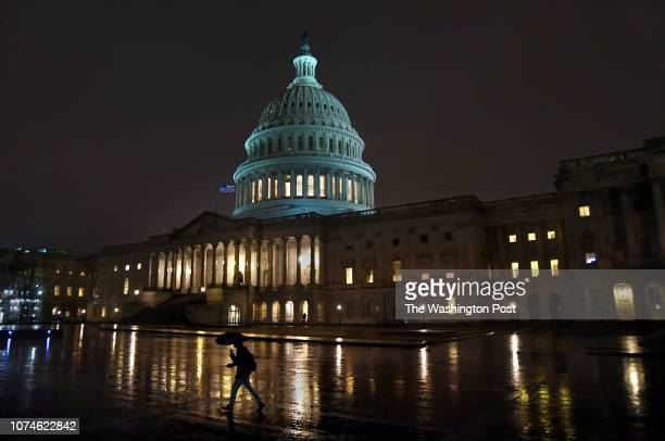 A walks away from the US Capitol building in the rain having just left the Senate side near 1100pm Thursday night Most of the Capitol building...