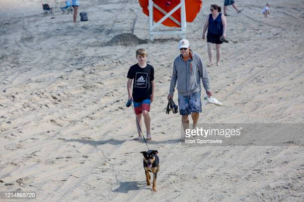A walks his dog barefoot on the beach on May 22 in Virginia Beach VA This is the first day of the beach's reopening for swimming sunbathing and...