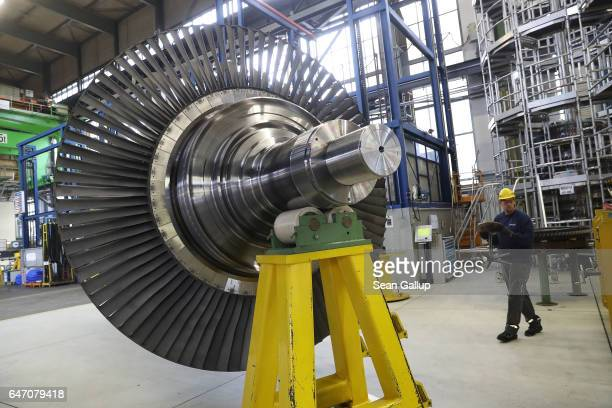 A walks past a turbine at the Siemens gas turbine factory on March 2 2017 in Berlin Germany Germany's number of unemployed fell by 15000 in February...