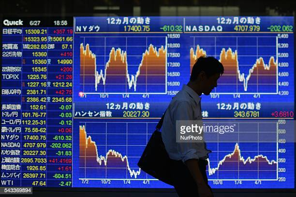 A walks past an electronic board showing the graphs of the recent fluctuations of Japan's Nikkei average outside a brokerage in Tokyo Japan June 27...
