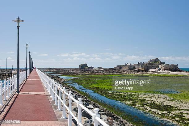 Walkway along the side of Elizabeth Marina, looking towards Elizabeth Castle in St Aubins Bay, St Helier, Jersey, Channel Islands