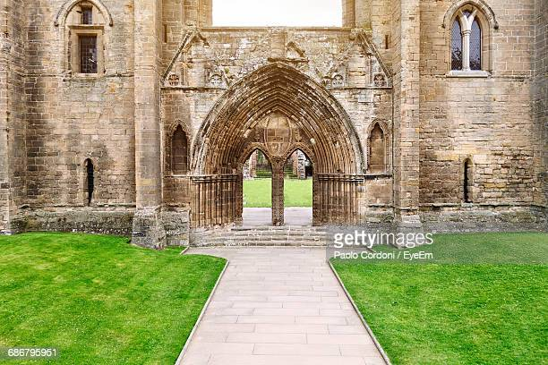 Walkway Amidst Field Against Elgin Cathedral