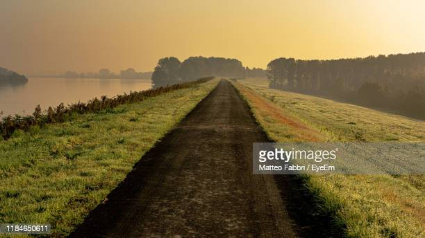 walkway amidst field against sky during sunset - ferrara stock pictures, royalty-free photos & images