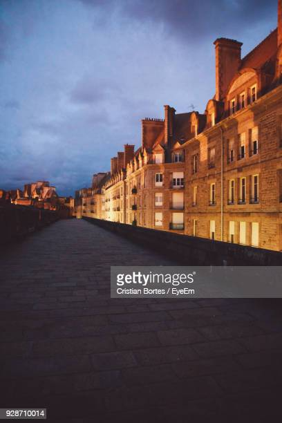 Walkway By Illuminated Buildings Against Cloudy Sky At Dusk