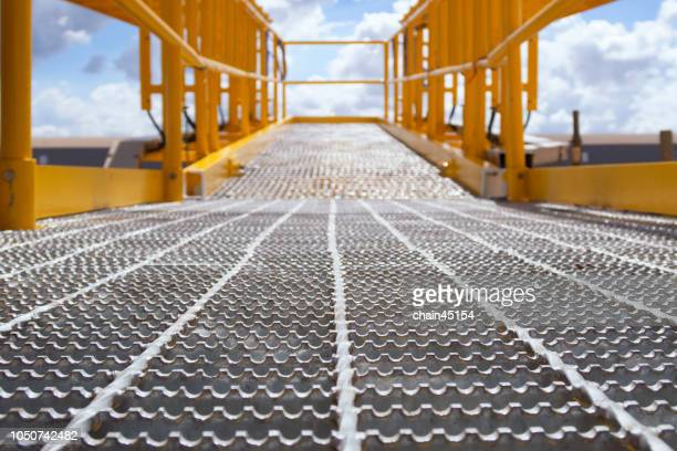 Walkway fare boom on oil and gas platform drilling rig for produced crude oil, natural gas and water in offshore or gulf, petroleum field. Industry concept of oil petroleum industry.