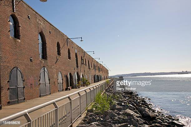 Walkway in front of historic building near water.