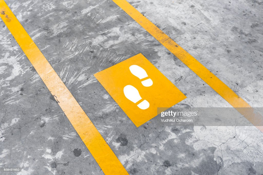 Walkway lane in parking building. Painted yellow footsteps between parallel yellow lines on abstract cement floor. : Stock Photo