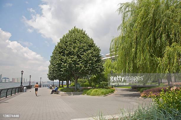 walkway near robert f. wagner jr. park, showing jogger and people on benches overlooking hudson river, downtown manhattan, new york - sloppy joe, jr stockfoto's en -beelden