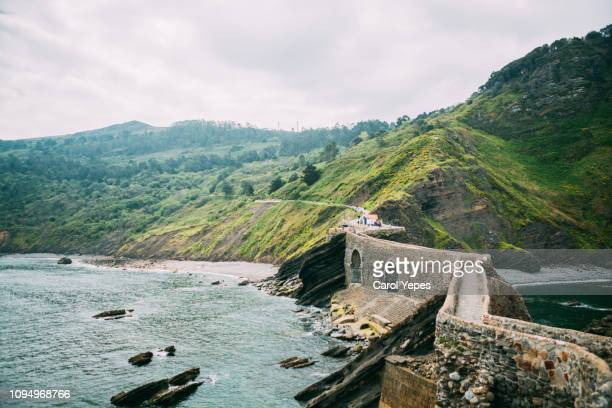 walkway to island of san juan de gaztelugatxe from hilltop of island. - bilbao stockfoto's en -beelden