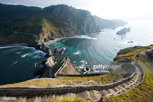 walkway to island of san juan de gaztelugatxe from hilltop of island. - バスク州 ストックフォトと画像