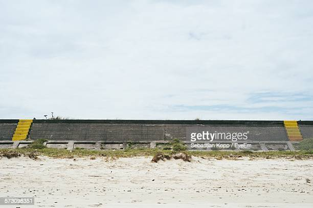 Wall At Beach Against Cloudy Sky