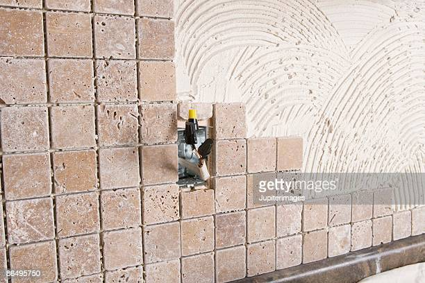 Wall being tiled over grout