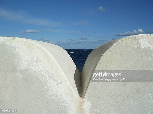 wall by sea against sky - carolina fragapane stock pictures, royalty-free photos & images