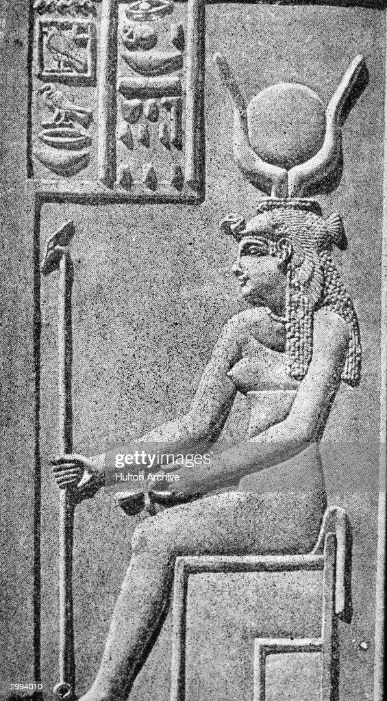 Wall carving of Egyptian goddess Isis, the goddess of fertility, wearing a headdress with a solar disk between cow horns.