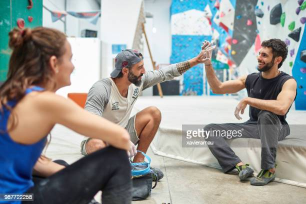 Wall climbers giving high-five by woman in gym