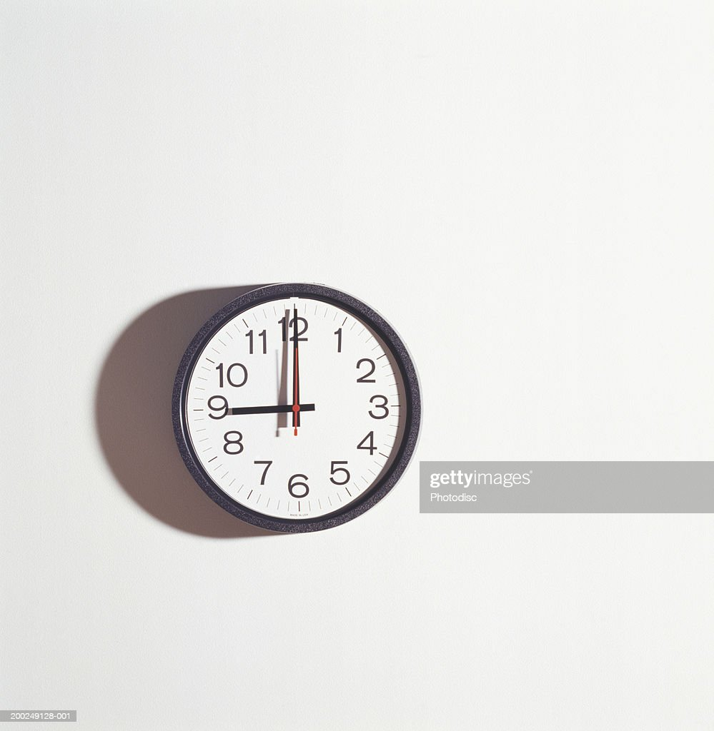 Wall clock on white wall : Stock Photo