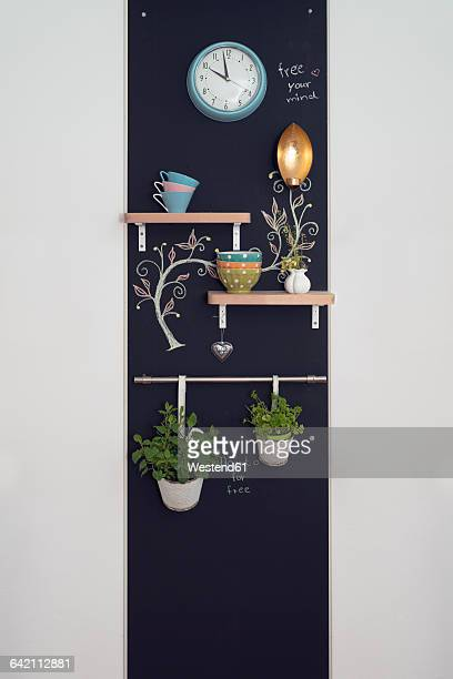 Wall decoration with shelves and herbs on blackboards with lamp and clock