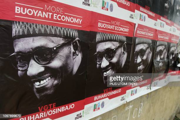 A wall is covered of campaign posters picturing candidate and actual Nigeria's President Mohammadu Buhari seeking a reelection for the Nigerian...