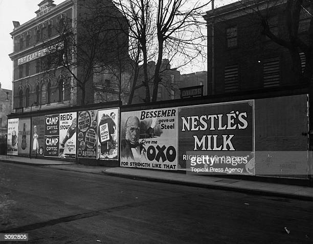 A wall of posters in Camberwell London advertising various products such as Nestle's Milk Oxo Camp Coffee and Marmite