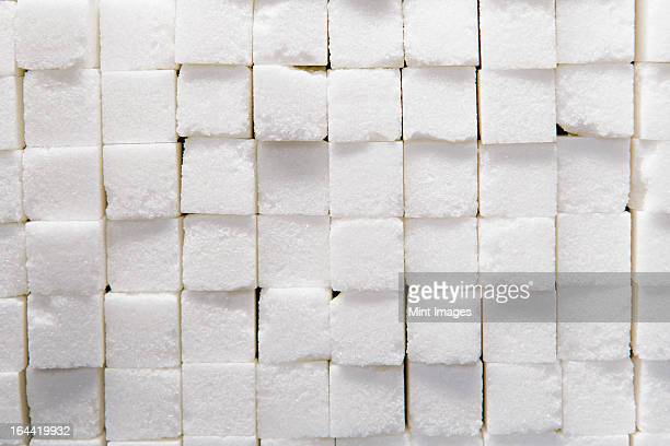 wall of stacked sugar cubes - sugar pile stock pictures, royalty-free photos & images