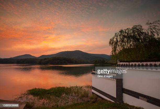 wall on lakeshore at sunset, nanjing, jiangsu province, china - image stock pictures, royalty-free photos & images