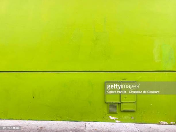 wall painted green and bright with electrical cabinets and sidewalk - green colour ストックフォトと画像
