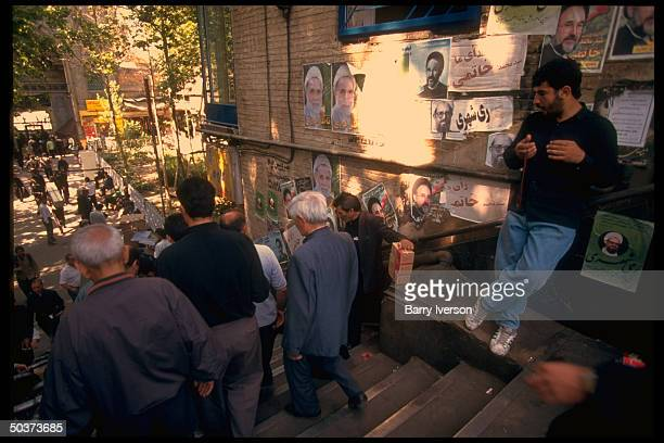Wall plastered w. Presidential election campaign posters incl. For conservative candidate Ali Akbar Nateq-Noori strung overhead & moderate...
