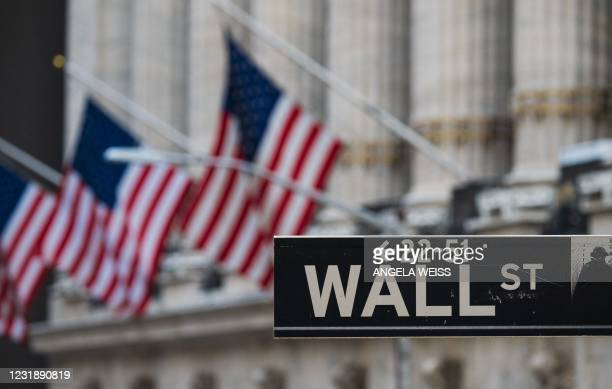 Wall St sign hangs at the New York Stock Exchange at Wall Street on March 23, 2021 in New York City. - Wall Street stocks were under pressure early...