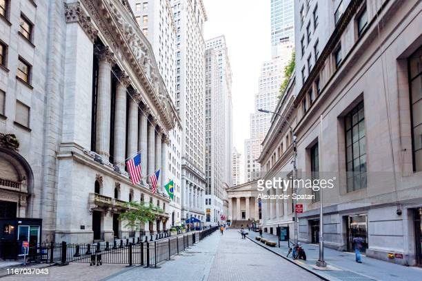 wall street and new york stock exchange in downtown manhattan, new york city, usa - new york stock exchange stock pictures, royalty-free photos & images