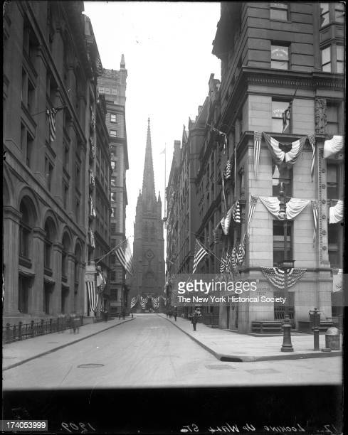 Wall Street looking west from Nassau Street toward Trinity Church several buildings including the Manhattan Trust Company draped with flagsNew York...