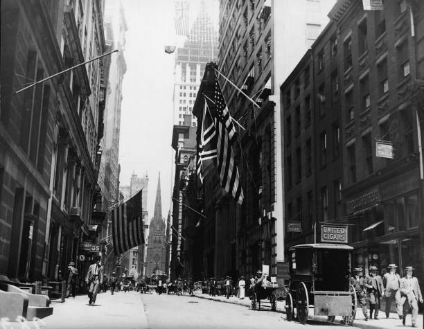 Pedestrians and horse-drawn carriages on Wall Street,...