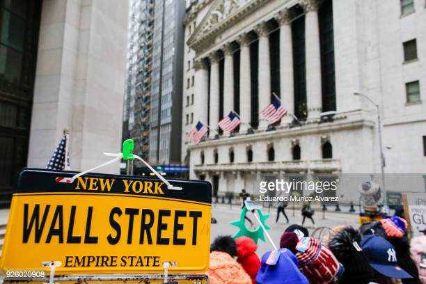 A wall Street plate is seen while pedestrians pass in front of the New York Stock Exchange on March 1 2018 in New York City Major stock indexes...
