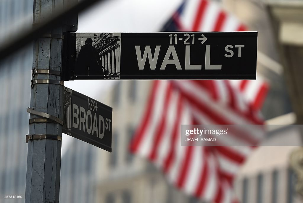 A Wall Street road sign is pictured near the New York Stock Exchange (NYSE) building on October 16, 2014 in New York. US stocks dropped sharply in early trade Thursday, following international markets downward as anxiety over global growth continued to prompt selling. About 30 minutes into trade, the Dow Jones Industrial Average stood at 16,062.34, down 79.40 points (0.49 percent). AFP PHOTO/Jewel Samad