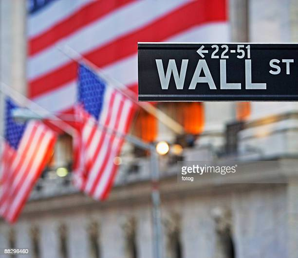 wall street sign and american flags - wall street stock-fotos und bilder