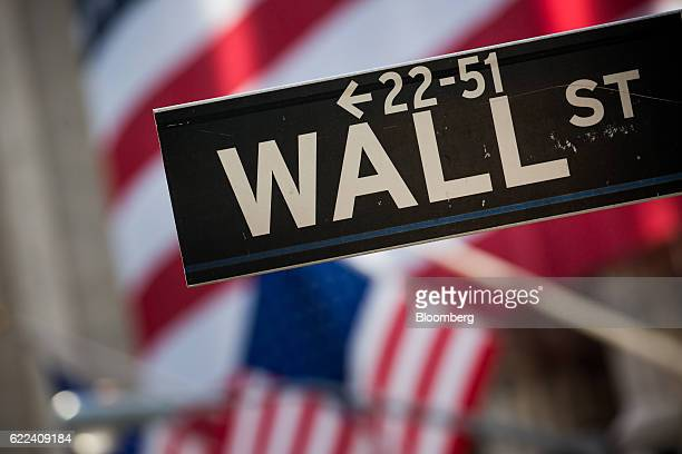 A Wall Street sign is displayed in front of the New York Stock Exchange in New York US on Friday Nov 11 2016 US stocks fluctuated in whipsaw trading...