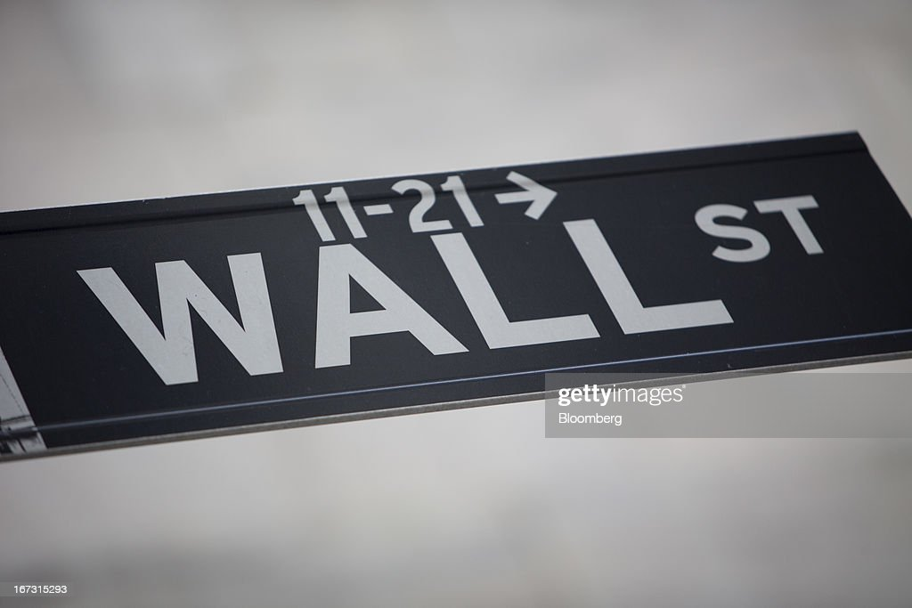 A Wall Street sign is posted in front of the New York Stock Exchange (NYSE) in New York, U.S., on Wednesday, April 24, 2013. U.S. stocks were little changed, after the Standard & Poor's 500 Index gained for a third day, as investors watched earnings at companies from Boeing Co. to Apple Inc. Photographer: Scott Eells/Bloomberg via Getty Images