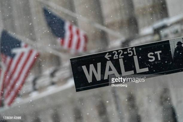 Wall Street street sign outside the New York Stock Exchange as snow falls in New York, U.S., on Monday, Feb. 1, 2021. Winter Storm Orlena will snarl...