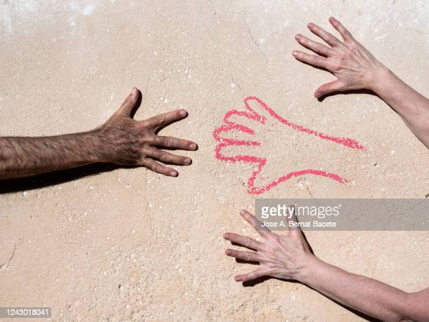 wall with a hand drawn and a human hand looking for the union. - dessin erotique photos et images de collection