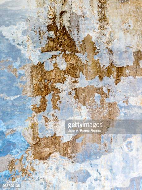 Wall with peeling blue and white paint with cracks and dampness. High resolution photography.