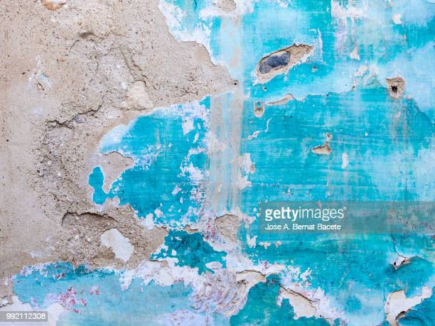 Wall with peeling blue and white paint with cracks and dampness.